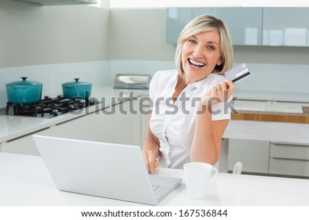 Cheerful woman doing online shopping through laptop and credit card in the kitchen at home - stock photo