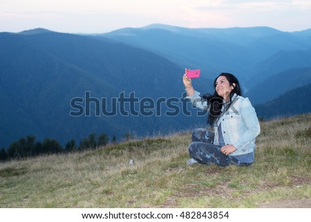 Cheerful woman doing selfie by phone mobile  in the mountains