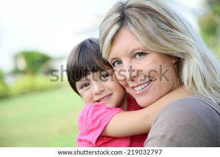Cheerful woman embracing little girl in arms