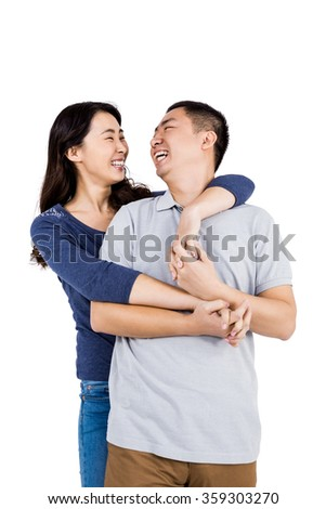 Cheerful woman embracing man against white background