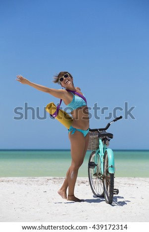 Cheerful woman enjoying a day at the beach, with a bike and a yoga mat - stock photo