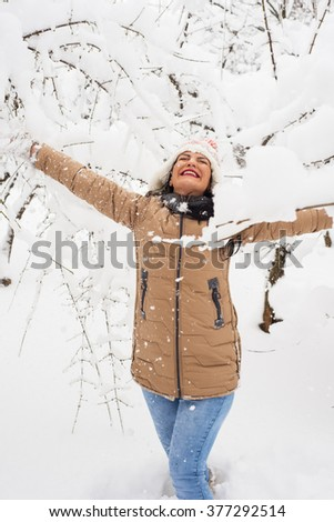 Cheerful woman enjoying snow in the park - stock photo