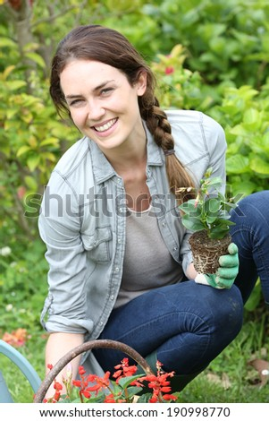 Cheerful woman gardening at home in springtime - stock photo