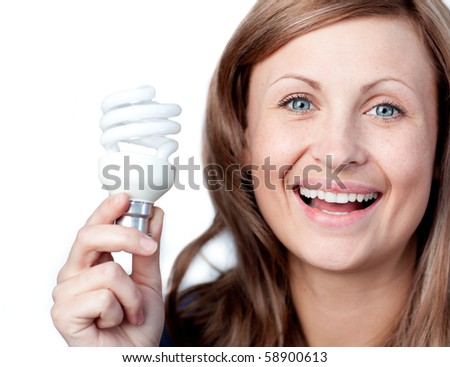 Cheerful woman holding a light bulb against white background - stock photo