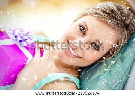 Cheerful woman holding a present against snow falling - stock photo