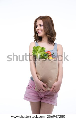 Cheerful woman holding a shopping bag full of groceries and looking away - stock photo