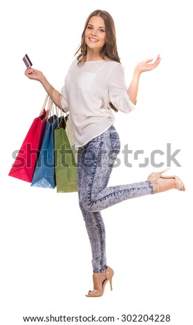 Cheerful woman holding colored shopping bags and credit card on white background. - stock photo