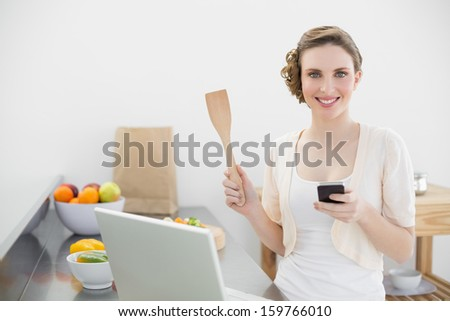 Cheerful woman holding her smartphone standing in the kitchen smiling at camera - stock photo