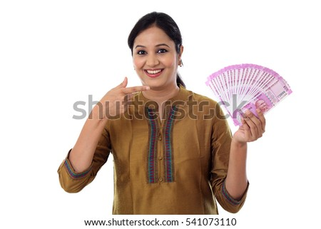 Cheerful woman holding Indian currency notes with thumb up gesture