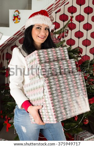 Cheerful woman holding many Christmas gifts in front of natural tree