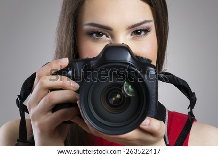 Cheerful woman holding photo camera