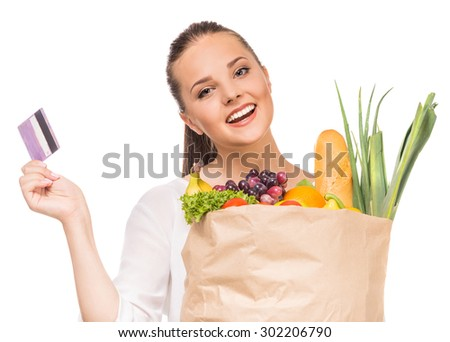 Cheerful woman holding shopping bag full of fresh food and credit card on white background.