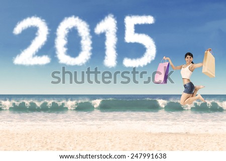 Cheerful woman holding shopping bag jumping at beach celebrate new year of 2015 - stock photo