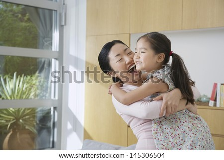Cheerful woman hugging her daughter in the living room - stock photo