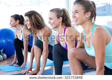 Cheerful woman in fitness studio doing lunge pose on exercise mat