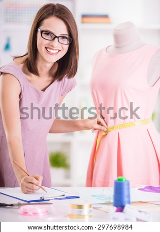 Cheerful woman in glasses measuring pink dress, looking at camera and writing it down. - stock photo