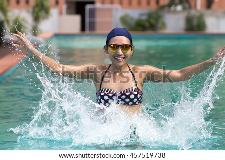 Cheerful woman in swimsuit and bathing cap jumps in the swim pool and splashing water.