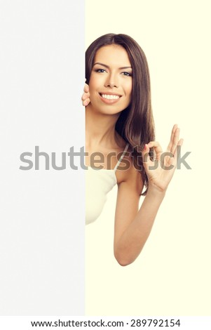 cheerful woman in tank top casual smart clothing, showing okay hand sign gesture or zero, over empty blank signboard with copyspace area for text or slogan - stock photo