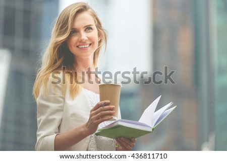 Cheerful woman in the street drinking coffee