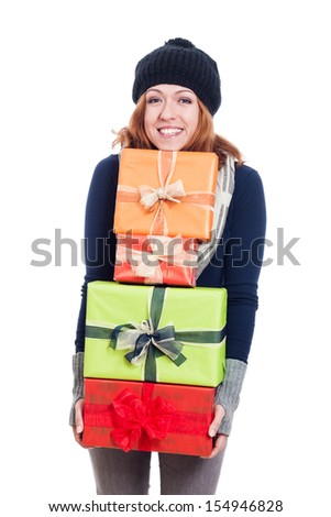 Cheerful woman in winter clothes holding many presents, isolated on white background. - stock photo