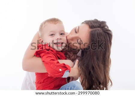 Cheerful woman is embracing and kissing her son with love. The boy is smiling and looking forward with enjoyment. Isolated on background - stock photo