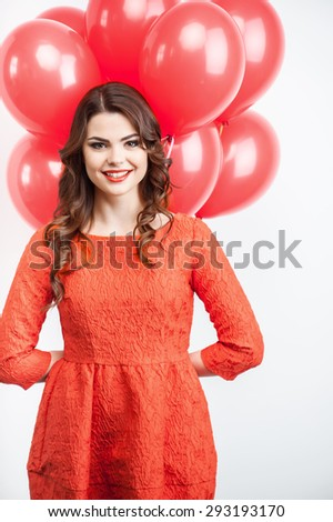 Cheerful woman is holding red balloons behind her back. She is standing and smiling.  Isolated on grey background - stock photo