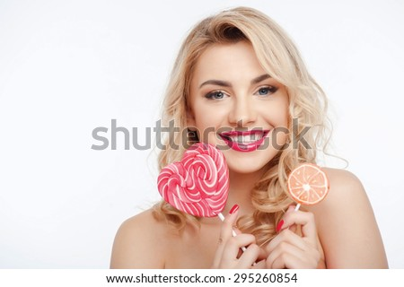 Cheerful woman is holding two lollipops in both her hands. She is smiling with happiness. Isolated on background and there is copy space in left side - stock photo