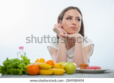 Cheerful woman is looking aside thoughtfully. She can not decide what should eat. Fruits and vegetables or donuts. The lady is sitting at the table. Isolated on a white background - stock photo