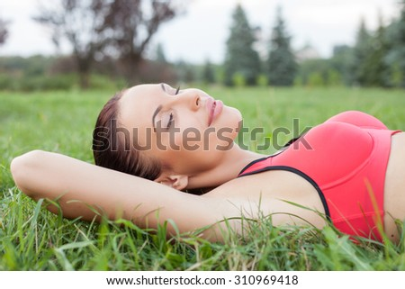 Cheerful woman is lying on grass in park. She is resting and smiling. The sportswoman closed her eyes with enjoyment. She is wearing sport clothing - stock photo