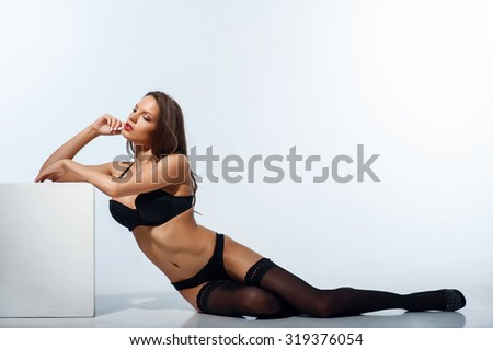 Cheerful woman is sitting and leaning on surface. She is wearing black underwear and high heels. The girl is looking aside with desire. Isolated on background - stock photo