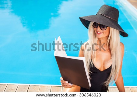 Cheerful woman is sitting near a swimming pool. She is reading a book and relaxing. The lady is sunbathing and smiling. Copy space in left side - stock photo