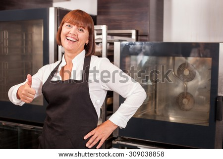 Cheerful woman is standing in bakery and giving thumb up. She is smiling and looking forward with happiness. The senior chef is wearing an apron. Copy space in right side - stock photo