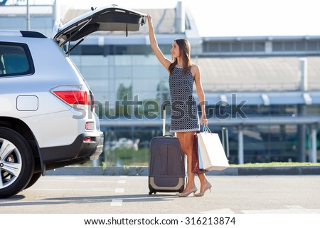 Cheerful woman is standing near her car and closing the trunk. She is holding many packets of bought things and smiling. There is a suitcase near her. Copy space in right side - stock photo