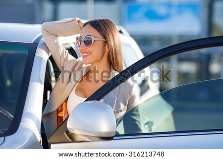 Cheerful woman is standing near her car and relaxing. She is opening the door and looking forward happily. The lady is smiling. She is wearing sunglasses - stock photo