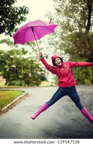 Cheerful woman jumping with umbrella - stock photo