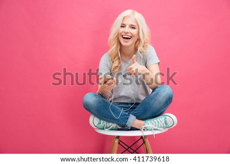 Cheerful woman listening music in headphones and showing thumb up over pink background - stock photo