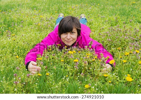 Cheerful woman lying on a flower meadow - stock photo