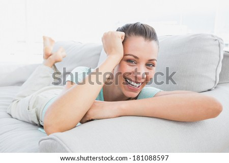 Cheerful woman lying on couch smiling at camera at home in the living room