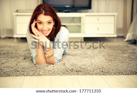 Cheerful woman lying on the carpet at home - stock photo