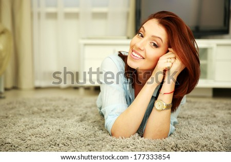 Cheerful woman lying on the floor at home - stock photo