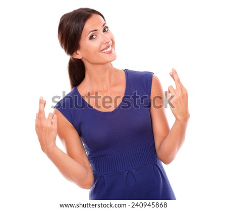 Cheerful woman making a wish and luck sign while looking at you in white background - stock photo