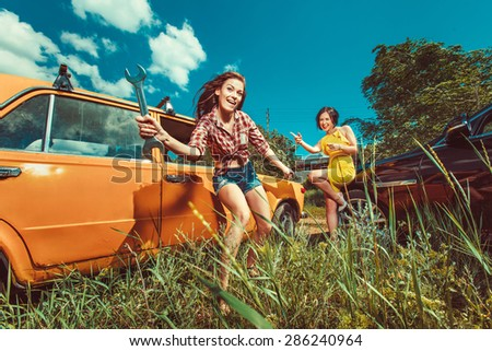 Cheerful woman mechanic is repairing a car with the wrench another woman is watching. - stock photo