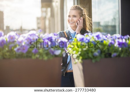 Cheerful woman on the phone in city center - stock photo