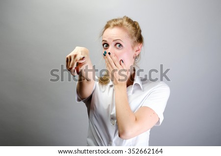 Cheerful woman pointing finger towards camera - stock photo