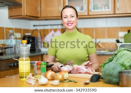 Cheerful woman preparing meal in kitchen and smiling - stock photo