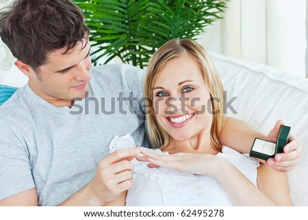 Cheerful woman receiving a wedding ring after a proposal at home smiling at the camera