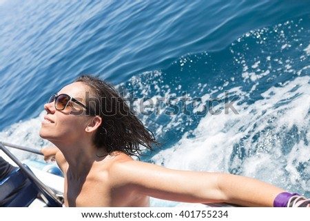 Cheerful woman relaxing and taking tan with eyes closed on edge of boat - stock photo