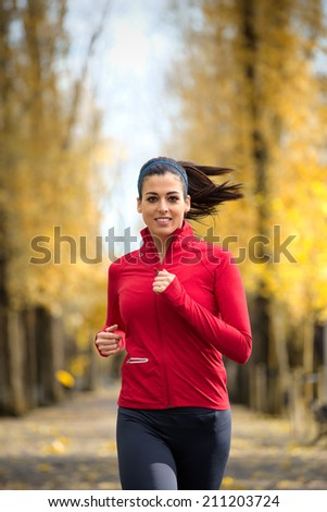 Cheerful woman running in autumn at city park. Female athlete on fall season training outdoor. Caucasian brunette runner. - stock photo