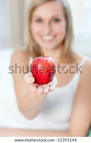 Cheerful woman showing an apple at home
