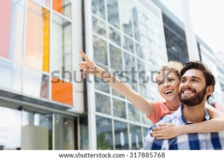 Cheerful woman showing something to man while enjoying piggyback ride in city - stock photo